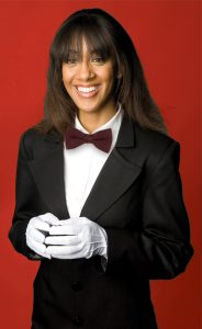 woman in blazer, bow-tie and white gloves